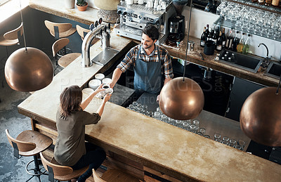 Buy stock photo High angle shot of a cheerful young barman giving a coffee to a customer that she just payed for inside of a restaurant