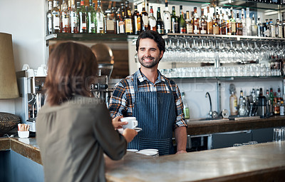 Buy stock photo Shot of a cheerful young barman giving a coffee to a customer that she just payed for inside of a restaurant