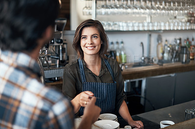 Buy stock photo Shot of a cheerful female bartender receiving a card as payment from a customer inside of a restaurant