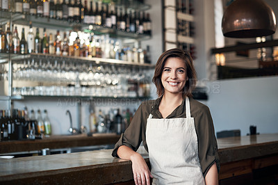Buy stock photo Portrait of a cheerful female bartender standing in front of the bar counter while looking at the camera