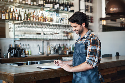 Buy stock photo Shot of a cheerful young male bartender making notes in a book while standing next to a bar counter