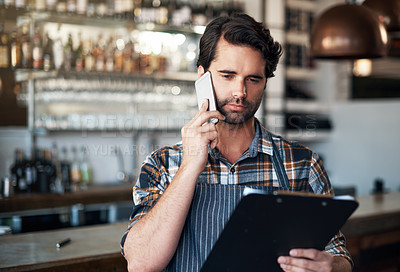 Buy stock photo Shot of a focused young male bartender making a call and contemplating while standing inside of a restaurant