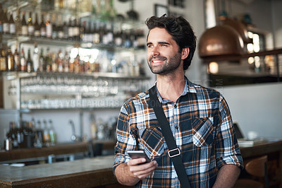 Buy stock photo Shot of a cheerful young man texting on his phone while standing in a restaurant