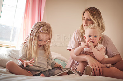 Buy stock photo Shot of a little girl using a digital tablet while bonding with her mother and sister on the bed