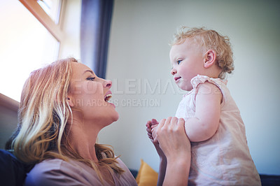 Buy stock photo Shot of an adorable baby girl bonding with her mother at home