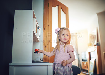 Buy stock photo Shot of an adorable little girl playing with a toy kitchen set at home