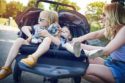 Buy stock photo Shot of a young woman putting her daughters into a pram on a day outdoors