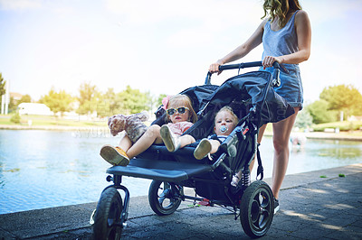 Buy stock photo Shot of a young woman pushing her daughters in a pram on a day outdoors