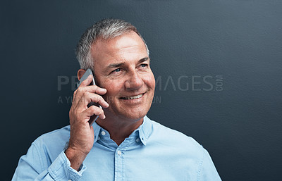 Buy stock photo Studio shot of a mature man using a mobile phone against a gray background