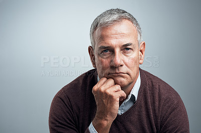 Buy stock photo Studio shot of a mature man looking serious against a gray background