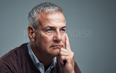 Buy stock photo Studio shot of a mature man looking thoughtful against a gray background