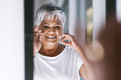 Buy stock photo Portrait of a cheerful mature woman flossing her teeth while looking into a mirror at home