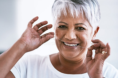 Buy stock photo Portrait of a cheerful mature woman flossing her teeth while looking at the camera at home