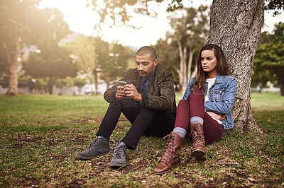 Buy stock photo Shot of a cheerful young man sitting down under a tree with his unhappy girlfriend while using his phone outside in a park
