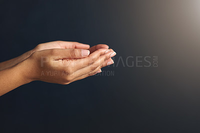 Buy stock photo Studio shot of an unrecognizable woman holding her hands together against a black background