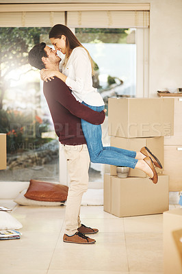 Buy stock photo Full length shot of an affectionate young couple embracing while moving into a new home