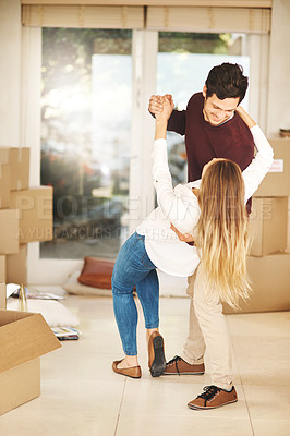 Buy stock photo Full length shot of an affectionate young couple dancing while moving into a new home