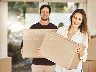 Buy stock photo Portrait of a smiling young couple carrying boxes while moving into their new home