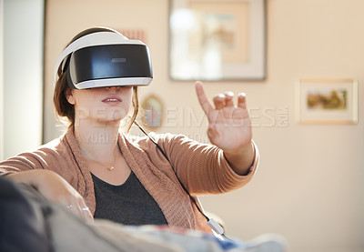 Buy stock photo Shot of a focused unrecognizable young woman having fun while wearing a virtual reality headset in her home