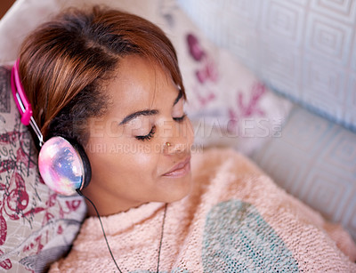 Buy stock photo Shot of an attractive young woman listening to music while relaxing on the sofa at home