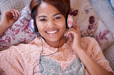 Buy stock photo High angle shot of an attractive young woman listening to music while relaxing on the sofa at home