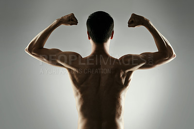 Buy stock photo Studio shot of an unrecognizable young sportsman flexing against a grey background