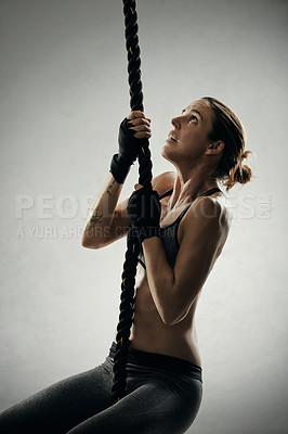Buy stock photo Studio shot of an athletic young sportswoman climbing rope against a grey background