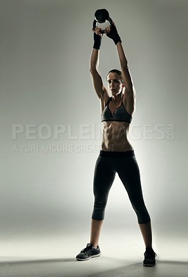 Buy stock photo Studio shot of an athletic young sportswoman working out with a kettle bell against a grey background