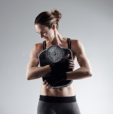 Buy stock photo Studio shot of an athletic young sportswoman clutching a weightscale against a grey background