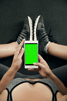 Buy stock photo Studio shot of an unrecognizable young sportswoman using her cellphone while sitting on an exercise mat