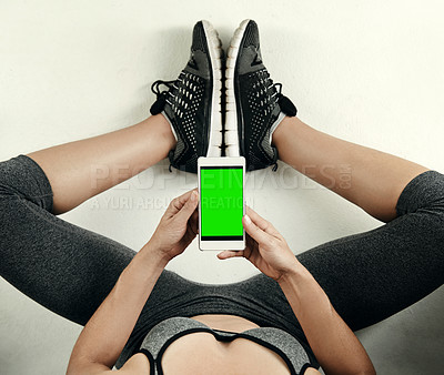 Buy stock photo Studio shot of an unrecognizable young sportswoman using her cellphone while sitting on the floor
