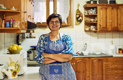 Buy stock photo Portrait of a cheerful mature woman standing with arms folded while looking into the camera in the kitchen at home
