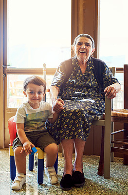Buy stock photo Portrait of a cheerful little boy sitting next his great grandmother while looking into the camera at home