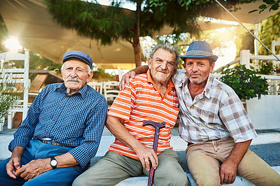 Buy stock photo Portrait of a group of cheerful senior men sitting together while looking into the camera outside