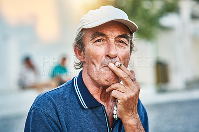Buy stock photo Portrait of a cheerful senior man  smoking a cigarette and standing outside while looking at the camera