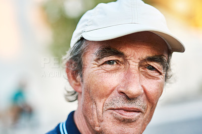 Buy stock photo Portrait of a cheerful senior man wearing a hat and standing outside while looking at the camera