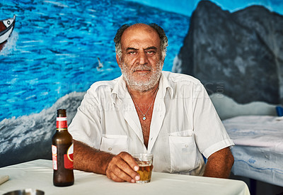 Buy stock photo Portrait of a confident senior man enjoying a beer while being seated in a cafe