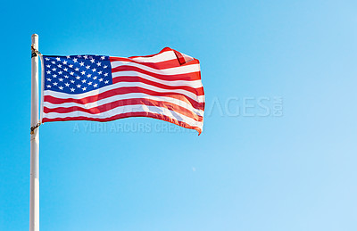 Buy stock photo Low angle shot of the American flag standing on its own outside during the day