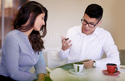 Buy stock photo Shot of two young businesspeople having a discussion in an office