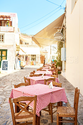 Buy stock photo Shot of a group of empty tables and chairs packed outside a restaurant during the day