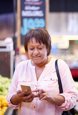 Buy stock photo Shot of a mature woman using a mobile phone in a grocery store