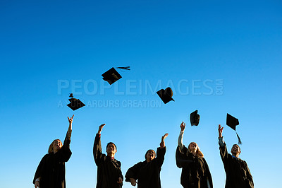 Buy stock photo Shot of a group of students throwing their hats in the air on graduation day