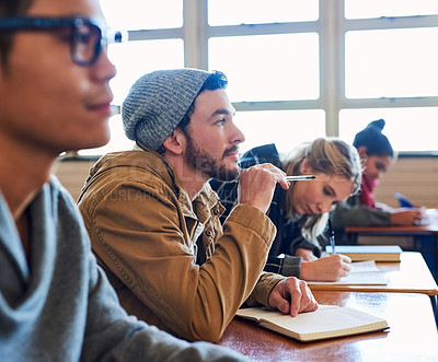 Buy stock photo Cropped shot of a group of university students working in class while sitting in a lecture
