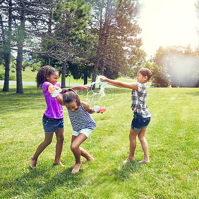 Buy stock photo Shot of adorable little girls playing with water balloons outdoors