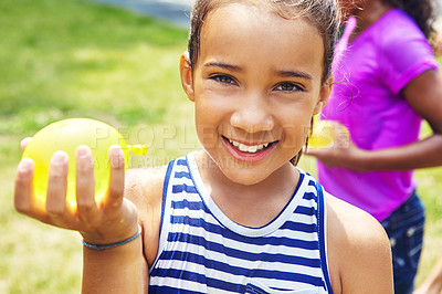 Buy stock photo Portrait of an adorable little girl playing with water balloons outdoors
