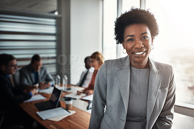 Buy stock photo Portrait of a confident young businesswoman standing in an office with her colleagues in the background
