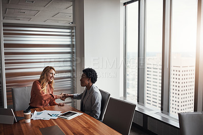 Buy stock photo Shot of two businesswoman shaking hands in an office