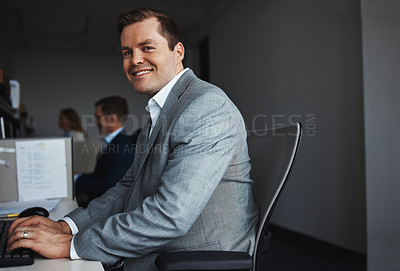Buy stock photo Shot of a businessman sitting at his desk with colleagues in the background