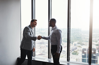Buy stock photo High angle of two corporate businessmen shaking hands during a meeting in the boardroom