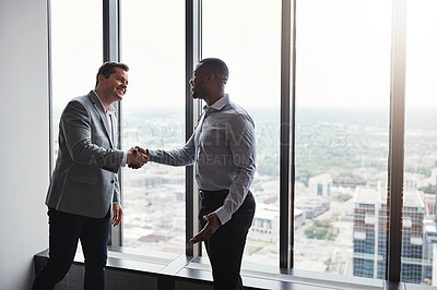 Buy stock photo High angle shot of two corporate businessmen shaking hands during a meeting in the boardroom